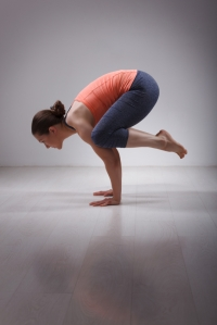Beautiful sporty fit yogini woman practices yoga asana kakasana - crow pose in studio