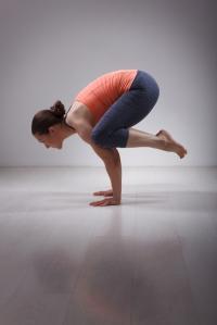 Beautiful sporty fit yogini woman practices yoga asana kakasana - crow pose in studio